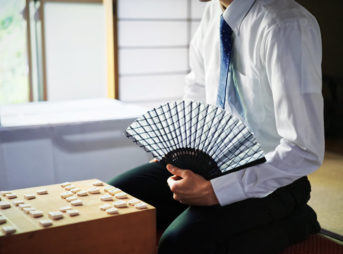 将棋盤の前で扇子を持って座る男性