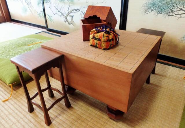和室で、駒袋と駒箱が乗った将棋盤と駒台